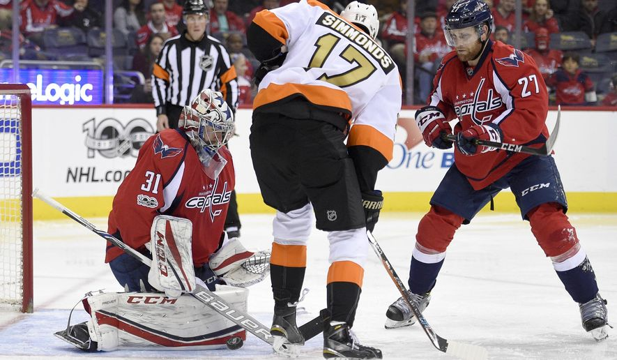 Washington Capitals goalie Philipp Grubauer (31), of Germany, stops the puck against Philadelphia Flyers right wing Wayne Simmonds (17) during the second period of an NHL hockey game, Sunday, Jan. 15, 2017, in Washington. Capitals defenseman Karl Alzner (27) looks on. (AP Photo/Nick Wass)