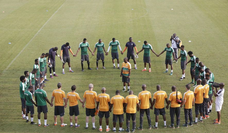 Ivory Coast's soccer team and team officials form a human ring during their training session in Stade Akoakam Oyem, Gabon, Sunday, Jan. 15, 2017, ahead of their African Cup of Nations Group C soccer match against Togo. (AP Photo/Sunday Alamba)