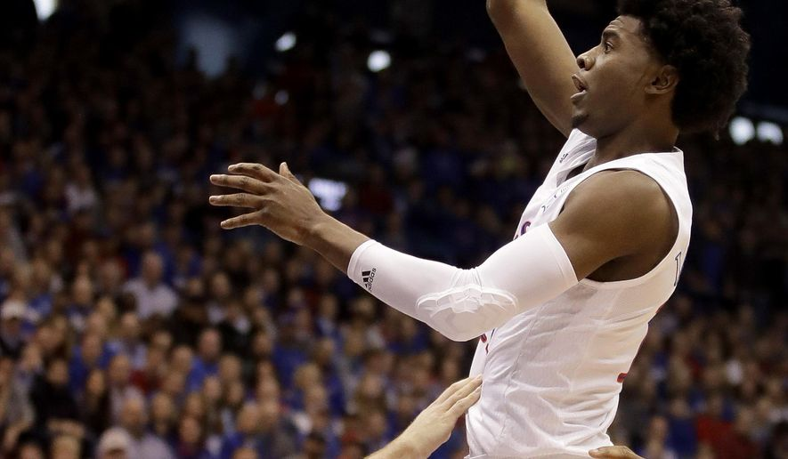 Kansas' Josh Jackson, right, shots over Oklahoma State's Phil Forte III (13) during the first half of an NCAA college basketball game, Saturday, Jan. 14, 2017, in Lawrence, Kan. (AP Photo/Charlie Riedel)