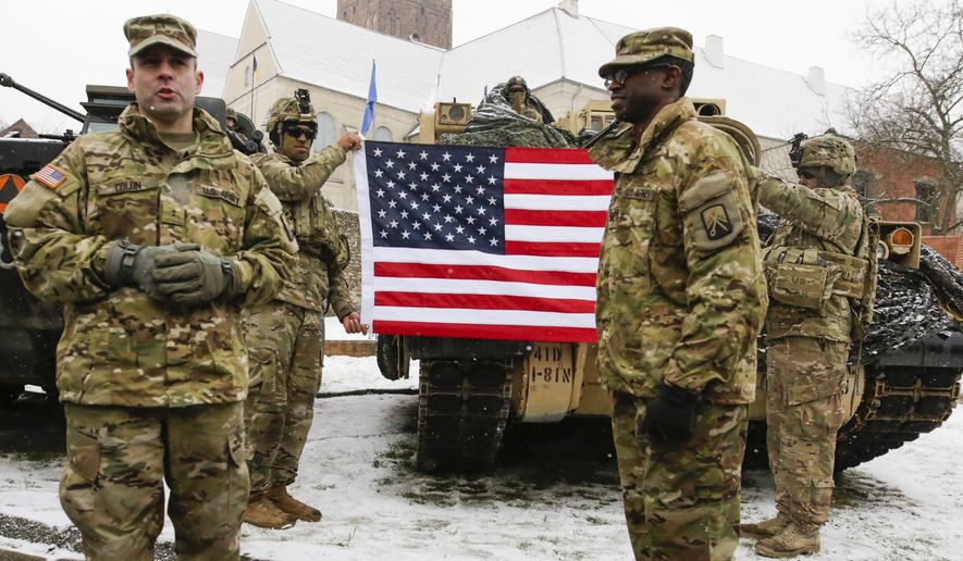 U.S. Army soldiers hold an American flag as they attend the official welcoming ceremony of the U.S. troops in Zagan, Poland, Saturday, Jan. 14, 2017. The ceremony comes 23 years after the last Soviet troops left Poland and also marks a new historic moment — the first time any Western forces are being deployed on a continuous basis to NATO's eastern flank. (AP Photo/Krzysztof Zatycki)
