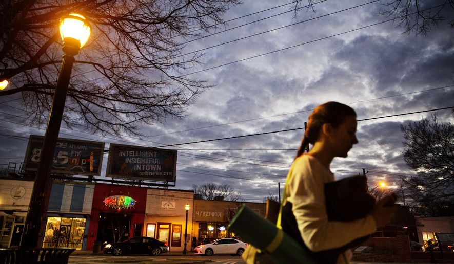 ADVANCE FOR USE TUESDAY, JAN. 17, 2017 AND THEREAFTER-A woman heads to a yoga class as dusk falls in East Atlanta, Ga., in Dekalb County, Wednesday, Jan. 11, 2017. The county is a Democratic stronghold east of downtown Atlanta. Hillary Clinton won four out of five DeKalb votes, capitalizing on a heavy African-American population, a burgeoning Hispanic community and a bevy of white liberals, many of them from elsewhere. (AP Photo/David Goldman)