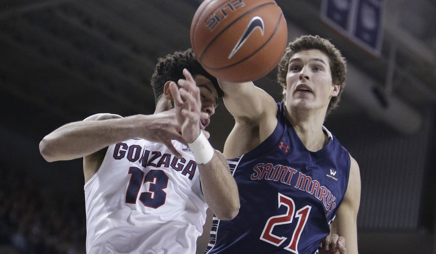 Gonzaga guard Josh Perkins (13) and Saint Mary's center Evan Fitzner (21) go after the ball during the first half of an NCAA college basketball game in Spokane, Wash., Saturday, Jan. 14, 2017. (AP Photo/Young Kwak)