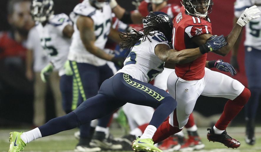 Seattle Seahawks cornerback Richard Sherman (25) tackles Atlanta Falcons wide receiver Julio Jones (11) during the second half of an NFL football divisional football game, Saturday, Jan. 14, 2017, in Atlanta. (AP Photo/John Bazemore)