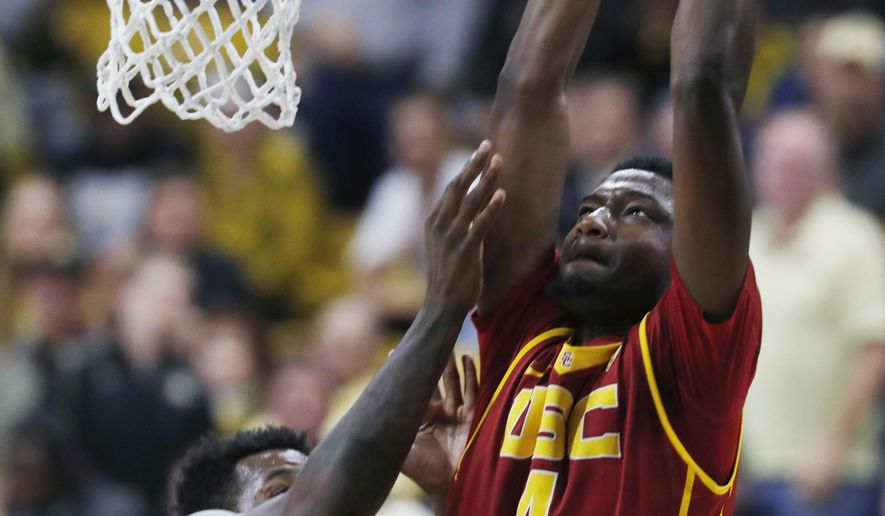 USC forward Chimezie Metu, right, dunks over Colorado forward Wesley Gordon in the first half of an NCAA college basketball game Sunday, Jan. 15, 2017, in Boulder, Colo. (AP Photo/David Zalubowski)