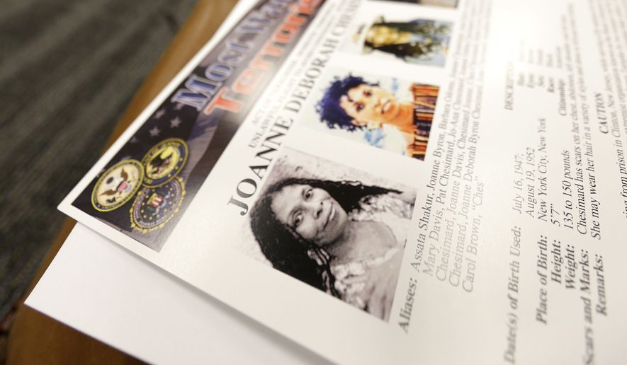 A handout with photographs of Joanne Chesimard, a fugitive for more than 30 years, is seen on top of a reporter's bag during a news conference giving updates on the search of Chesimard, Thursday, May 2, 2013, in Newark, N.J. The reward for the capture and return of convicted murderer Chesimard, one of New Jersey's most notorious fugitives, was doubled to $2 million Thursday on the 40th anniversary of the violent confrontation that led to the slaying of a New Jersey state trooper.  The FBI also announced it has made Chesimard, now living in Cuba as Assata Shakur, the first woman on its list of most wanted terrorists.  (AP Photo/Julio Cortez)