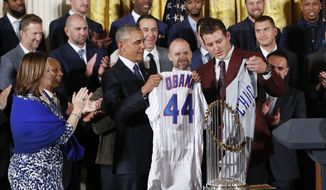 President Barack Obama holds up a personalized Chicago Cubs baseball jersey presented to him by Anthony Rizzo, right, during a ceremony in the East Room of the White House in Washington, Monday, Jan. 16, 2017, where the president honored the 2016 World Series Champion baseball team. (AP Photo/Pablo Martinez Monsivais)