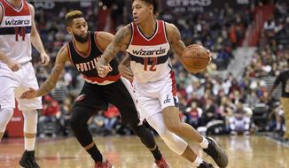 Washington Wizards forward Kelly Oubre Jr. (12) dribbles against Portland Trail Blazers guard Allen Crabbe (23) during the second half of an NBA basketball game, Monday, Jan. 16, 2017, in Washington. The Wizards won 120-101. (AP Photo/Nick Wass)