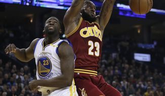 Cleveland Cavaliers' LeBron James, right, scores over Golden State Warriors' Draymond Green during the first half of an NBA basketball game, Monday, Jan. 16, 2017, in Oakland, Calif. (AP Photo/Ben Margot)