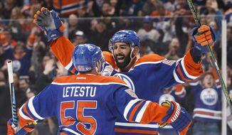 Edmonton Oilers' Mark Letestu (55) and Jujhar Khaira (54) celebrate a goal against the Arizona Coyotes during second period NHL hockey action in Edmonton, Alberta, Monday Jan. 16, 2017. (Jason Franson/The Canadian Press via AP)