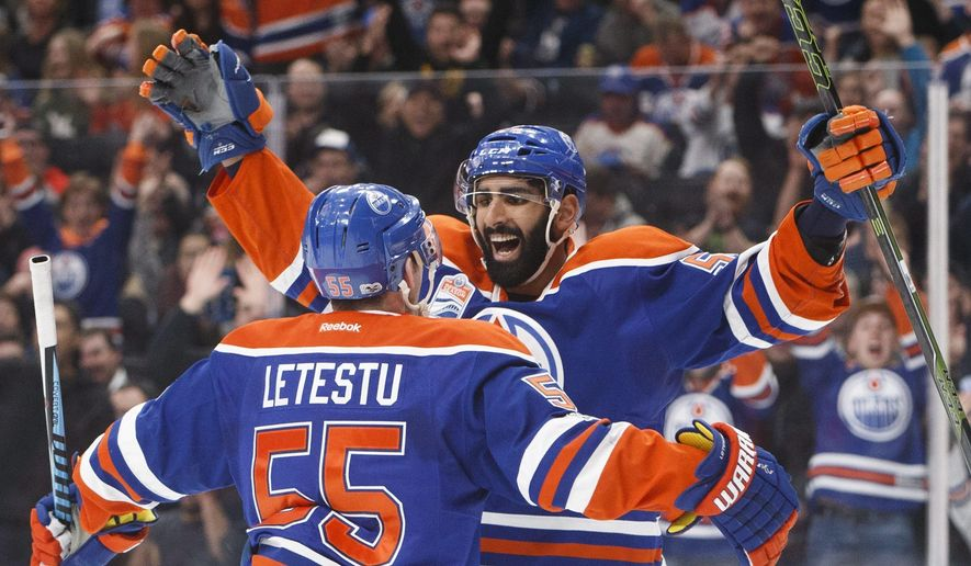 Edmonton Oilers' Mark Letestu (55) and Jujhar Khaira (54) celebrate a goal against the Arizona Coyotes during second period NHL hockey action in Edmonton, Alberta, Monday Jan. 16, 2017. (Jason Franson/The Canadian Press via AP)