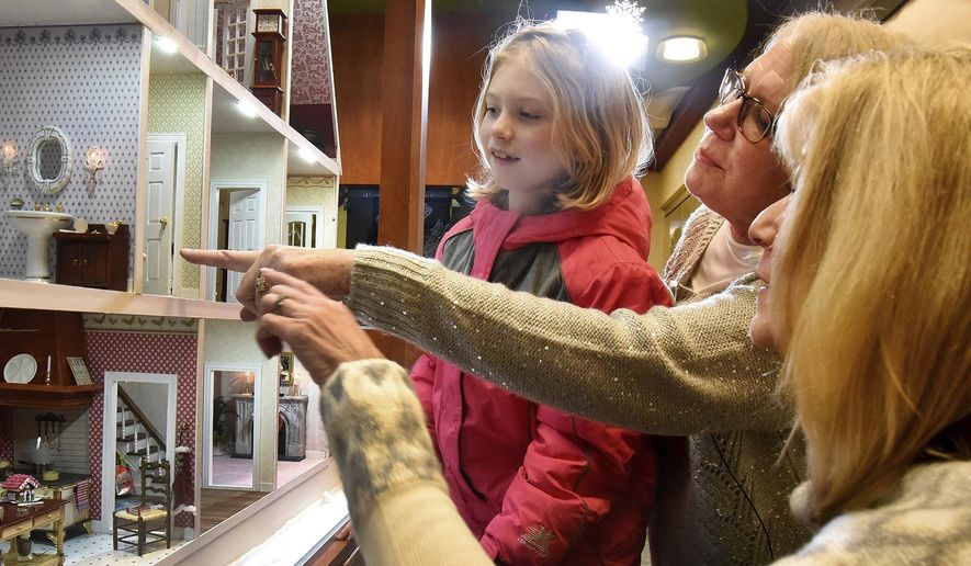 In this Dec. 20, 2016 photo, Child Life volunteers Susanne Frey, center, and Janice  Selden, show off the fully restored and outfitted dollhouse to 7-year-old patient Allison Sexton, at the Alexian Brothers Women's and Children's Hospital during its unveiling in Hoffman Estates, Ill. The donated 13-room, three-story Victorian dollhouse is an inspiration for recovering children at the hospital. (Bob Chwedyk/Daily Herald, via AP)