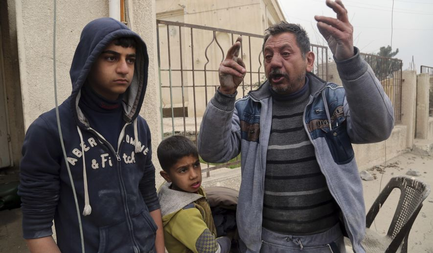 Thanon Yunus Yahya, right, chant slogans against Islamic State militia in a neighborhood recently liberated from the militia on the eastern side of Mosul, Iraq, Sunday, Jan. 15, 2017. Yahya claimed that his wife and son were previously executed by Islamic State militia. (AP Photo/ Khalid Mohammed)