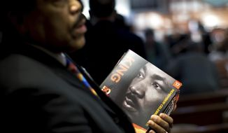 James R. Johnson hands out programs before the Rev. Martin Luther King Jr. holiday commemorative service at Ebenezer Baptist Church, Monday, Jan. 16, 2017, in Atlanta. (AP Photo/Branden Camp)