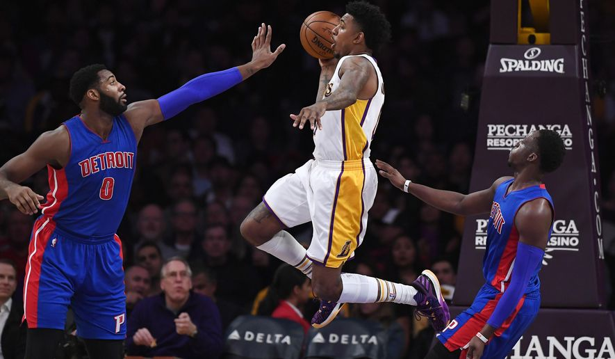 Los Angeles Lakers guard Nick Young, center, passes the ball as Detroit Pistons center Andre Drummond, left, and guard Reggie Jackson, of Italy, defend during the first half of an NBA basketball game, Sunday, Jan. 15, 2017, in Los Angeles. (AP Photo/Mark J. Terrill)