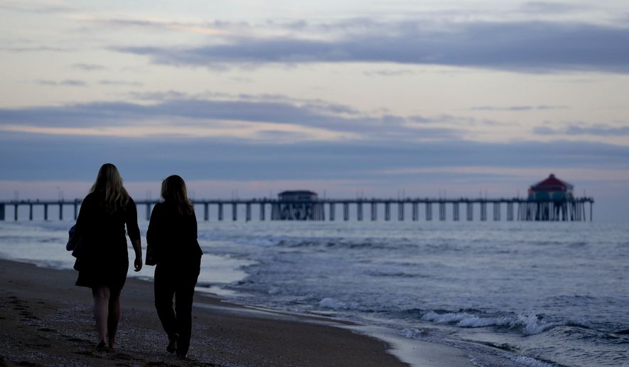 "ADVANCE FOR USE TUESDAY, JAN. 17, 2017 AND THEREAFTER- Catherine Johnson, left, and her mother, Bridget, walk in the sand along the shore of Huntington Beach, Calif., on Wednesday, Jan. 4, 2017. ""I'm excited because for the past eight years... we haven't had anything done because of the gridlock in Washington,"" says Catherine, 17, who served as Orange County chair of Students for Trump. ""A lot of people will get on board once they see that we're doing, instead of like crazy things, we're doing productive things that helps the country as a whole rather than helping one group."" Her mother, who is active in local Republican politics, agrees. ""Trump is a very hard worker and he's really going to get some work done rather than being the typical politician that just kicks the can down the road."" (AP Photo/Chris Carlson)"