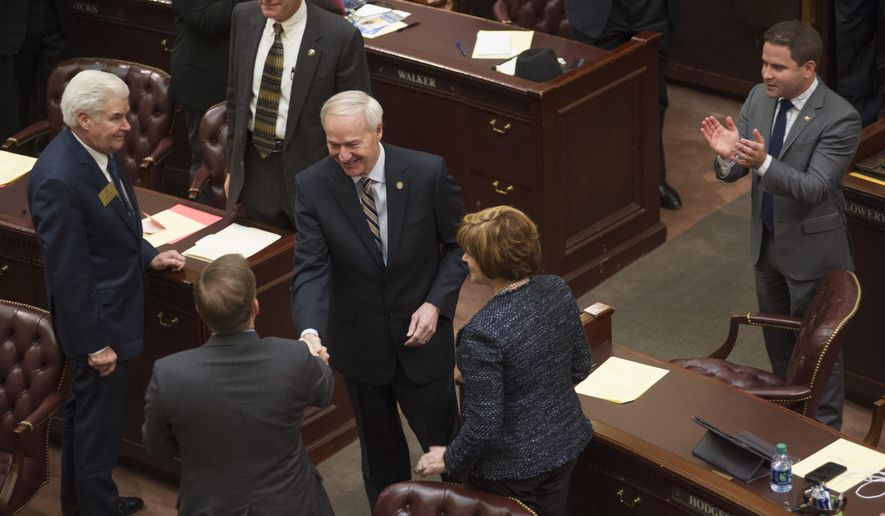 "FILE - In this Tuesday, Jan. 10, 2017, file photo, Arkansas Gov. Asa Hutchinson, center, greets legislators before his address to a joint session 91st General Assembly at the state Capitol in Little Rock, Ark. President-elect Donald Trump and congressional Republicans have pledged to cut federal taxes to boost the economy. But some GOP-controlled states have already adopted similar strategies, only to see growth falter and budget gaps widen. ""It does not take a Ph.D. in economics to know that we can't say yes to every spending need, and we should also not say yes to every tax-cut idea,"" Hutchinson warned late last year. (AP Photo/Brian Chilson, File)"