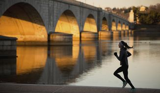 A jogger passes by the Arlington Memorial Bridge at sunrise in Washington on March 3, 2016. (Associated Press) **FILE**