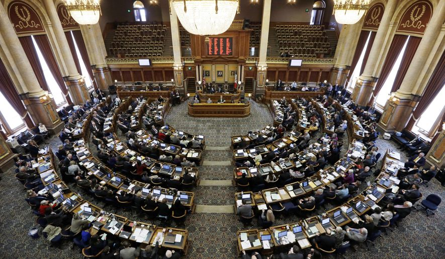 FILE - In this Jan. 13, 2014, file photo, state representatives work in the Iowa House on the opening day of the Iowa Legislature at the Statehouse in Des Moines, Iowa. Iowa lawmakers are considering a bill that would allow a woman who gets an abortion to sue the doctor who performed the procedure if she experiences emotional distress. If passed by the new GOP-controlled Legislature, the measure would be the first of its kind in the country and could make the state vulnerable to costly court challenges. (AP Photo/Charlie Neibergall, File)