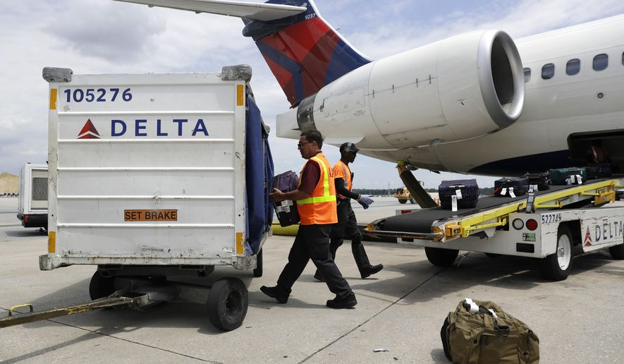 FILE - In this July 12, 2016, file photo, workers unload baggage from a Delta Air Lines flight at Baltimore-Washington International Thurgood Marshall Airport in Linthicum, Md. On Tuesday, Jan. 17, 2017, the federal Department of Transportation reported that U.S. airlines are improving on-time arrivals and canceling fewer flights. Hawaiian Airlines and Delta Air Lines posted the best rates for on-time arrivals. (AP Photo/Patrick Semansky, File)