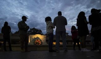 People visit the tomb of the Rev. Martin Luther King Jr. and his wife Coretta Scott King at sunset Monday, Jan. 16, 2017, in Atlanta. (AP Photo/Branden Camp)