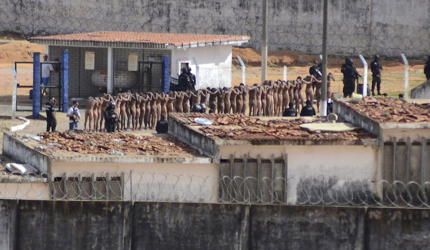 FILE - In this Jan. 15, 2017 file photo, inmates stand surrounded by police after a deadly prison riot at the Alcacuz prison in Nisia Floresta, Rio Grande do Norte state, Brazil. Brazilian authorities are scrambling to find ways to stop a wave of prison violence that has killed at least 125 inmates in two weeks, many decapitated and with their hearts and intestines ripped out. (Frankie Marcone/Futura Press via AP, File) NAO PUBLICAR NO BRASIL