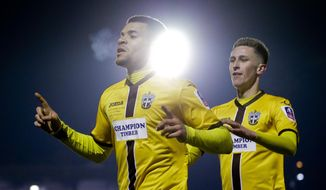 Sutton United's Maxime Biamou, left, celebrates after scoring his side's second goal of the game during the English FA Cup third round replay soccer match between AFC Wimbledon against Sutton United at Cherry Red Record stadium in south west London, Tuesday, Jan. 17, 2017 . (AP Photo/Alastair Grant)