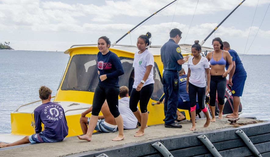 In this Monday, Jan. 16, 2017 photo, Kalani High School Paddling Team members arrive safely at Moanalua Bay in Hawaii-Kai, Hawaii, after their double-hull canoe began taking on water. All students returned to shore safely and no injuries were reported. (Craig T. Kojima/The Star-Advertiser via AP)