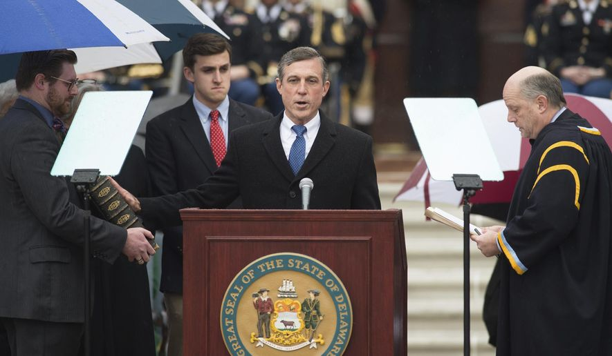 John C. Carney is sworn in as Delaware's governor by Chief Justice Leo E. Strine, Jr., during the inauguration ceremony at Legislative Hall in Dover, Del., Tuesday, Jan. 17, 2017. (Jason Minto/The Wilmington News-Journal via AP)