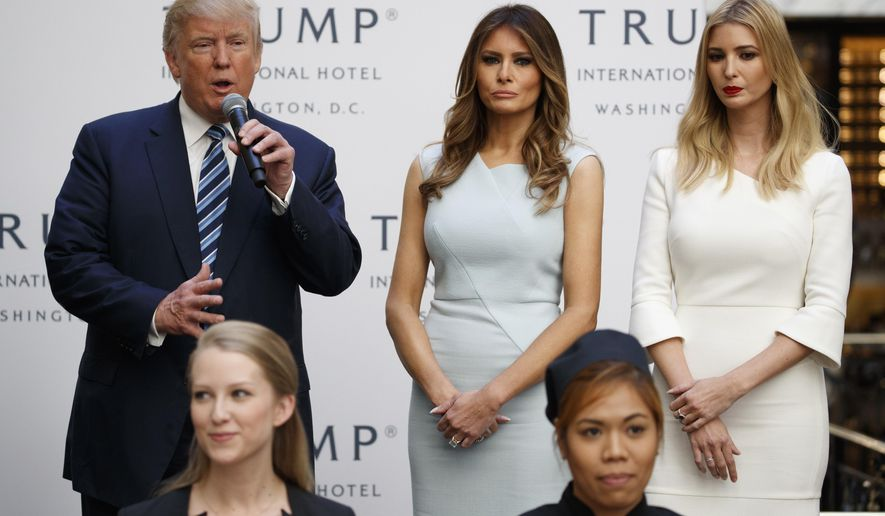 FILE - In this Oct. 26, 2016 file photo, Ivanka Trump, right, and Melania Trump, center, listen as then-Republican presidential candidate Donald Trump speaks during the grand opening of the Trump International Hotel- Old Post Office in Washington. People across the globe are always fascinated by what the incoming U.S. first lady is wearing to the inauguration. This time, as never before, the question is interlaced with politics, as designers have publicly grappled with the question of whether they would dress Melania Trump. Questions have also been raised about Ivanka Trump and her own label. (AP Photo/Evan Vucci, File)