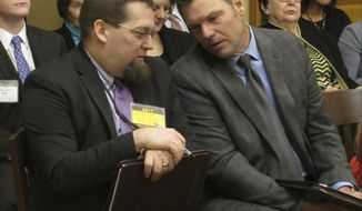 Kansas Secretary of State Kris Kobach, right, confers with Bryan Caskey, left, his elections director, during a state Senate committee hearing on a bill that would rewrite the state's rules for special congressional elections to give military personnel overseas more time to cast their ballots, in Topeka, Kan. The bill arose from President-elect Donald Trump's nomination of U.S. Rep. Mike Pompeo, R-Kan., as Central Intelligence Agency director. (AP Photo/John Hanna)