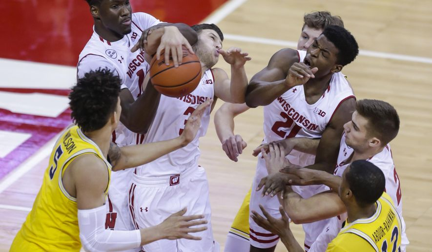 Michigan's D.J. Wilson (5) and Muhammad-Ali Abdur-Rahkman, right, and Wisconsin's Nigel Hayes (10), Zak Showalter and Khalil Iverson (21) vie for a rebound during the first half of an NCAA college basketball game Tuesday, Jan. 17, 2017, in Madison, Wis. (AP Photo/Andy Manis)