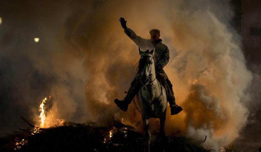 """A man rides a horse through a bonfire as part of a ritual in honour of Saint Anthony the Abbot, the patron saint of domestic animals, in San Bartolome de Pinares, about 100 km west of Madrid, Spain, on Monday, Jan. 16, 2017. On the eve of Saint Anthony's Day, hundreds ride their horses through the narrow cobblestone streets of the small village of San Bartolome during the """"Luminarias,"""" a tradition that dates back 500 years and is meant to purify the animals with the smoke of the bonfires and protect them for the year to come. (AP Photo/Emilio Morenatti)"""