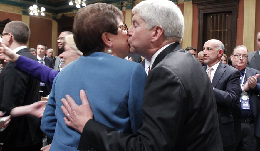 Michigan Gov. Rick Snyder, right, gives a smooch to his wife, Sue, as he enters the House Chambers to deliver his State of the State address to a joint session of the House and Senate, Tuesday, Jan. 17, 2017, at the state Capitol in Lansing, Mich. Snyder says he will try to persuade Republicans in Congress that the state's Medicaid expansion is a success and a model that can work nationally. (AP Photo/Al Goldis)