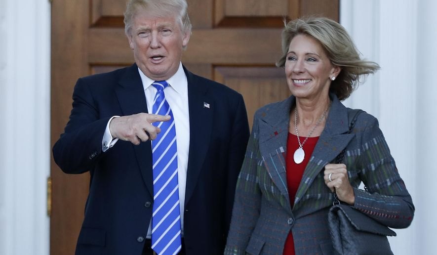 FILE - In this Nov. 19, 2016 file photo, President-elect Donald Trump stands with Education Secretary-designate Betsy DeVos in Bedminster, N.J.  DeVos has spent over two decades advocating for school choice programs, which give students and parents an alternative to traditional public school education. Her confirmation hearing was scheduled for Jan. 17. (AP Photo/Carolyn Kaster, File)