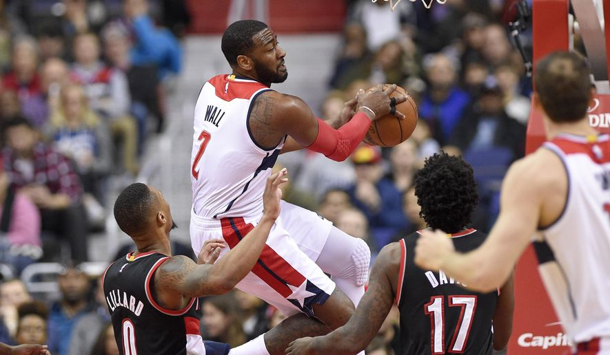FILE - In tbis Jan. 16, 2017 file photo, Washington Wizards guard John Wall (2) moves under the basket against Portland Trail Blazers guard Damian Lillard (0) and forward Ed Davis (17) during the first half of an NBA basketball game in Washington. The same fans who Wall once joked get more excited for a free chicken sandwich than a win are being treated to much more than that over the past month. (AP Photo/Nick Wass, File)