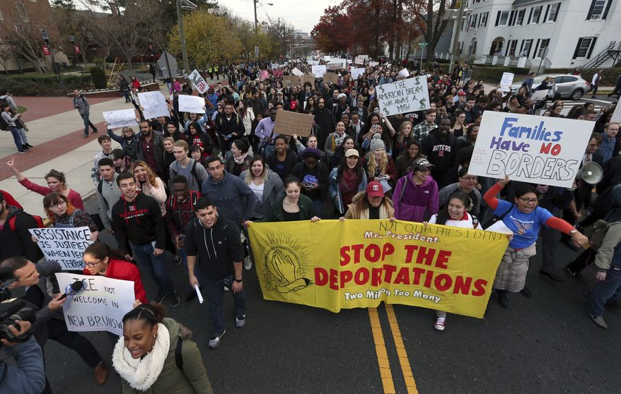 Hundreds of Rutgers University students block College Ave., in New Brunswick, N.J., as they march to protest some of President elect Donald Trump's policies and to ask school officials to denounce some of his plans at Rutgers University Wednesday, Nov. 16, 2016, in New Brunswick, N.J. College students at campuses around the United States say they are planning rallies and walkouts to call on school administrators to protect students and employees against immigration proceedings under Donald Trump's presidency. (AP Photo/Mel Evans)