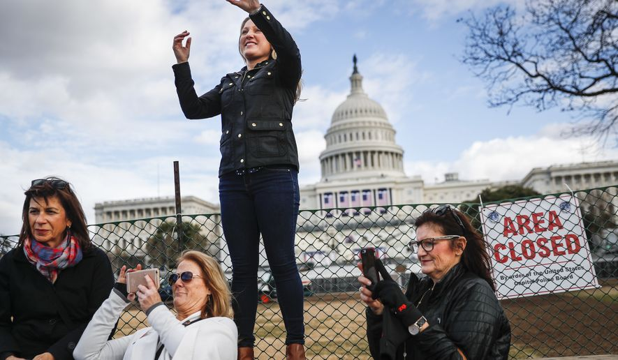 Micaela Johnson, of Leewood, Kan., in town to take part in Saturday's Women's March on Washington, takes a selfie with the Capitol Building in the background as preparations continue for Friday's presidential inauguration, Wednesday, Jan. 18, 2017, in Washington. (AP Photo/John Minchillo)