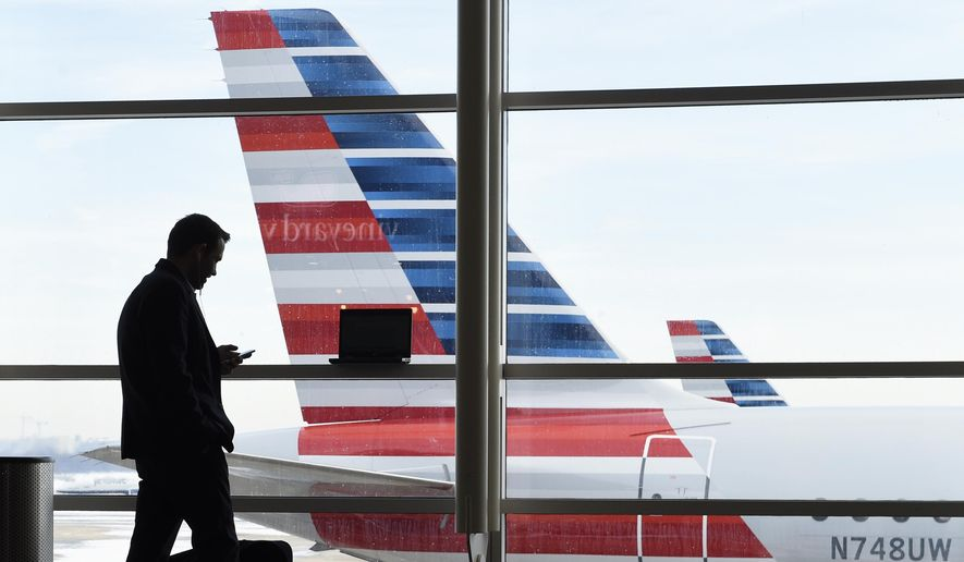 In this Jan. 25, 2016, file photo, a passenger talks on the phone as American Airlines jets sit parked at their gates at Washington's Ronald Reagan National Airport. (AP Photo/Susan Walsh, File)