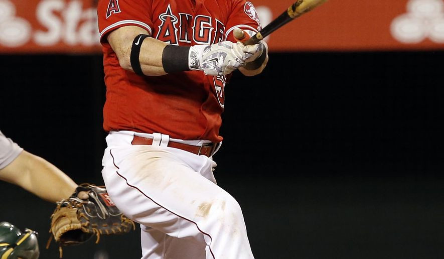 FILE - In this Sept. 28, 2016, file photo, Los Angeles Angels' Kole Calhoun follows his two-run home run against the Oakland Athletics during the fourth inning of a baseball game in Anaheim, Calif. Right fielder Kole Calhoun and the Los Angeles Angels have agreed to a $26 million, three-year contract. The sides reached agreement last week on a $6.35 million, one-year deal that avoided salary arbitration. As part of the deal announced Wednesday, Calhoun's 2017 pay is lowered to $6 million. (AP Photo/Alex Gallardo, File)