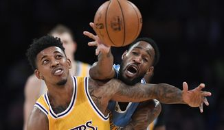 Los Angeles Lakers guard Nick Young, left, and Denver Nuggets guard Will Barton reach for the ball during the first half of an NBA basketball game, Tuesday, Jan. 17, 2017, in Los Angeles. (AP Photo/Mark J. Terrill)