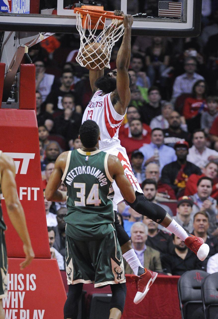 Houston Rockets guard James Harden (13) dunks as Milwaukee Bucks forward Giannis Antetokounmpo (34) looks on in the first half of an NBA basketball game, Wednesday, Jan. 18, 2017, in Houston. (AP Photo/Eric Christian Smith)