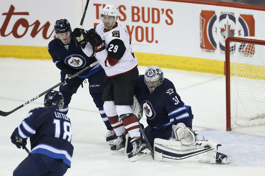 Winnipeg Jets goaltender Ondrej Pavelec (31) saves the shot as Jets' Jacob Trouba (8) and Arizona Coyotes' Brendan Perlini (29) jostle for position and Jets' Bryan Little (18) watches during the first period of an NHL hockey game Wednesday, Jan. 18, 2017, in Winnipeg, Manitoba. (John Woods/The Canadian Press via AP)