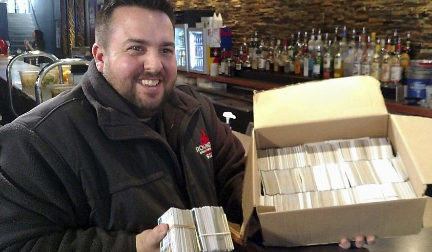 ADVANCE FOR SATURDAY, JAN. 21, 2017- In this Jan. 11, 2017 photo, Ryan Tucker, general manager of Rounders Sports Bar and Grill, displays the ID cards confiscated after would-be underage drinkers unsuccessfully attempted to enter the downtown Mankato, Minn., bar. The box was filled in a little more than a year. The cards in Tucker's hand are just from recent weeks. (Mark Fischenich /The Free Press via AP)