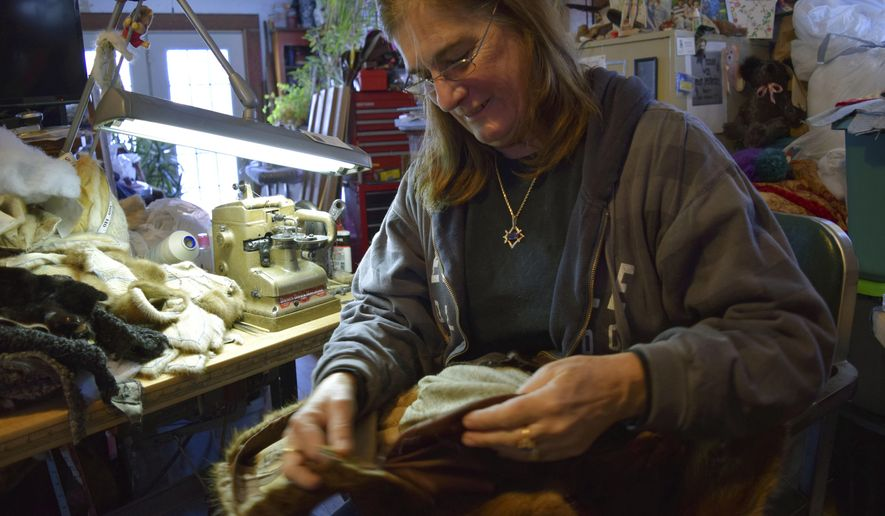 In this Dec. 15, 2016 photo, Susan McLoughlin sews in her Beloit, Wis., home. McLoughlin creates Teddy bears and other stuffed animals out of recycled fur coats. (Erica Pennington /The Beloit Daily News via AP)