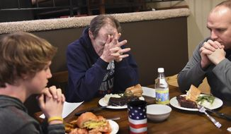 In this Wednesday, Jan. 11, 2017 photo, William Tentis, center, and Eric Reetz pray with Reetz's son, Ethan, 14, left, before eating dinner at Reetz's house in White Bear Township, Minn. Tentis, a homeless man, gave Reetz, a St. Paul, Minn. police officer, Christmas gifts and Reetz was so touched that he invited the man over to his house for dinner. (Jean Pieri /Pioneer Press via AP)