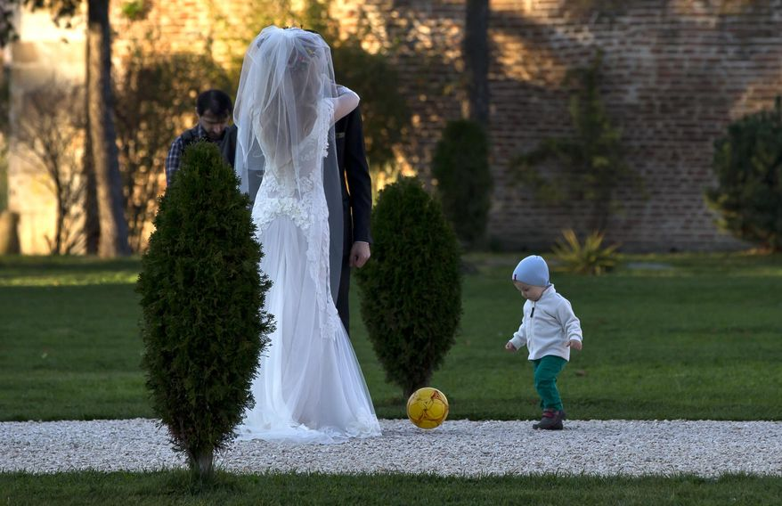 FILE - In this Nov. 9, 2013 file photo, a child plays with a ball next to a couple posing for a photographer in a park outside Bucharest, Romania. Newlywed couples took advantage of the unusual warm weather for the month of November, with temperatures reaching 20 degrees Celsius (68 degrees Fahrenheit), for outdoor photo sessions. Kiss goodbye some of those postcard-perfect, ideal-for-outdoor-wedding days. A new study said global warming is going to steal some of those exceedingly pleasant weather days from our future. On average, Earth will have four fewer days of mild and mostly dry weather by 2035 and ten fewer of them by the end of the century, according to a first-of-its-kind projection of nice weather. (AP Photo/Vadim Ghirda, File)