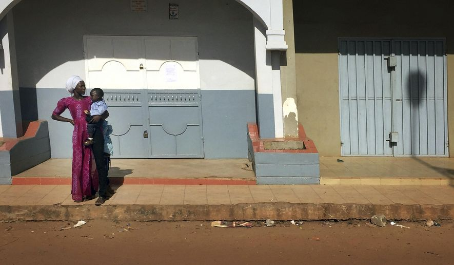 A woman looks down an empty street in Banjul, in Gambia, Wednesday Jan. 18, 2017. Special flights were being organized Wednesday to evacuate British and other tourists from Gambia, where the threat of a regional military intervention loomed as President Yahya Jammeh's mandate expires on Thursday after he lost elections in December. On Tuesday, he declared a state of emergency before he is supposed to cede power to President-elect Adama Barrow. (AP Photo)