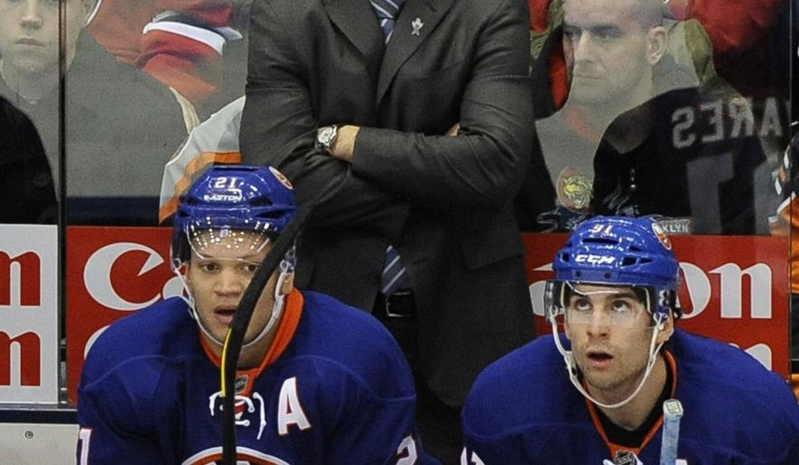 FILE - In this Saturday, Jan. 19, 2013 file photo, New York Islanders assistant coach Doug Weight watches the action from the bench during an NHL hockey game against the New Jersey Devils at the Nassau Coliseum in Uniondale, N.Y.  Doug Weight knows it won't be easy for New York Islanders to get back in the playoff race, but the interim coach is preaching a simple approach in taking it one game at a time with half the season remaining, Wednesday, Jan. 18, 2017. (AP Photo/Kathy Kmonicek, File)