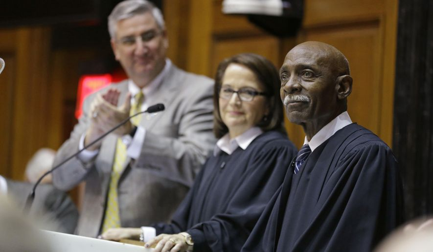 Indiana Supreme Court Justice Robert Rucker, right, is introduced after Chief Justice Loretta H. Rush, center, announced his impending retirement as she delivered her State of the Judiciary address to a joint session of the legislature at the Statehouse in Indianapolis, Wednesday, Jan. 18, 2017. Gov. Eric Holcomb is at the left. Rucker will retire this year after 18 years on the court.  (AP Photo/Michael Conroy)