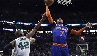 New York Knicks forward Carmelo Anthony (7) grabs a rebound over Boston Celtics center Al Horford (42) during the first quarter of an NBA basketball game in Boston, Wednesday, Jan. 18, 2017. (AP Photo/Charles Krupa)